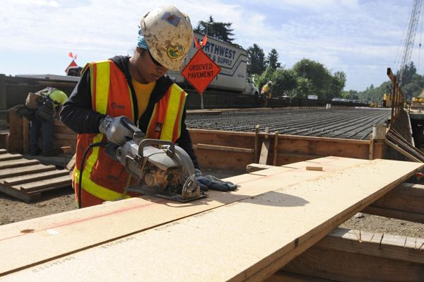 Nikki Santiago, an apprentice carpenter with Wildish Standard Paving Co. and a member of Carpenters Local 156, cuts pieces for concrete slab formwork at the site of the Southwest Iowa Street Viaduct Replacement project in Portland on Tuesday.