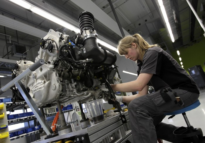 Female working on a automobile mechanical engine